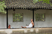 A Chinese man rests in the Humble Administrator's garden in Suzhou, China.