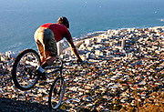 For once off publishing use in Argus Cycle Tour South Africa magazine. By copyright to Greg Beadle. Andrew Guess (26) of Gardens rides his trial bicycle on the granite outcrop, on the slopes of Lion's Head above the Atlantic Seaboard, in Cape Town. Mountain bike trials, also known as observed trials is a discipline of mountain biking in which the rider attempts to pass through an obstacle course without setting foot to ground. Derived from motorcycle trials, it originated in Spain and is said to have been invented by the father of Ot Pi, a world champion motorcycle trials rider. Pi's father had wanted his son to learn motorcycle trials by practising on an ordinary push bike..Trials riding is an extreme test of bicycle handling skills, over all kinds of obstacles, both natural and man-made. It now has a strong -- though small -- following worldwide, though it is still primarily a European sport. Skills taken from trials riding can be used practically on any bicycle for balance, for example controlled braking and track standing, or balancing on the bike without putting a foot down. Competition trial bikes are characterised by powerful brakes, wide handlebars, lightweight parts, single-speed low gearing, low tyre pressures with a thick rear tire, distinctive frame geometry, and typically a lack of seat. Andrew is one of a handful of trial riders in South Africa. Picture by Greg Beadle