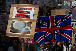 """© Licensed to London News Pictures . 13/07/2018. London, UK. Placard reading """" Trump would make tea like this """" illustrated by a cup of extremely pale, milky tea . Demonstrators march from Portland Place to Trafalgar Square in protest against US President Donald Trump's UK visit . Photo credit: Joel Goodman/LNP"""