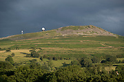 Radar station on top of Titterstone Clee Hill on 21st July 2020 in Cleedownton, United Kingdom. Titterstone Clee Hill, sometimes referred to as Titterstone Clee or, incorrectly, Clee Hill, is a prominent hill in the rural English county of Shropshire, rising at the summit to 533 metres above sea level. It is one of the Clee Hills, in the Shropshire Hills Area of Outstanding Natural Beauty. Most of the summit of the hill is affected by man-made activity, the result of hill fort construction during the Bronze and Iron Ages and, more recently, by years of mining for coal and quarrying for dolerite, known locally as dhustone, for use in road-building. Many derelict quarry buildings scattered over the hill are of industrial archaeological interest as very early examples of the use of reinforced concrete. Several radar domes and towers operate on the summit of the hill. The largest of the radar arrays is part of the National Air Traffic Services NATS radar network, and covers one of 30 overlapping regions of UK airspace. The one on Titterstone Clee monitors all aircraft within a 100-mile radius.