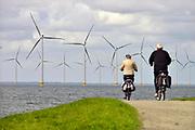 Nederland, the Netherlands, Urk, 9-5-2017 NOP Agrowind, energiebedrijf RWE Essent en Westermeerwind exploiteren een windpark op land en in het water van het IJsselmeer. De stroomproducent bouwde hier windmolens die 5 megawatt op land, en 3 megawatt op zee produceren. Siemens leverde turbines. Mensen, recreanten rijden op de fiets langs het water. Recreatie,ouderen,senioren,ontspanning,bewegen,fietsers,uitwaaien, FOTO: FLIP FRANSSEN