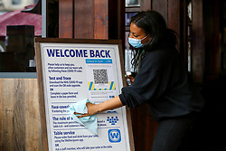 © Licensed to London News Pictures. 16/05/2021. London, UK. A staff member cleans the 'Welcome Back' information board at The Toll Gate - JD Wetherspoon pub in north London, ahead of indoor reopening. On Monday 17 May, pubs and restaurants will welcome back customers indoors for the first time in more than five months, as Covid-19 restrictions are eased. Photo credit: Dinendra Haria/LNP