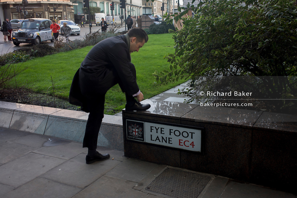 A businessman stoops down to tie a shoelace, resting his leg in Fye Foot Lane EC4 in the financial City of London.