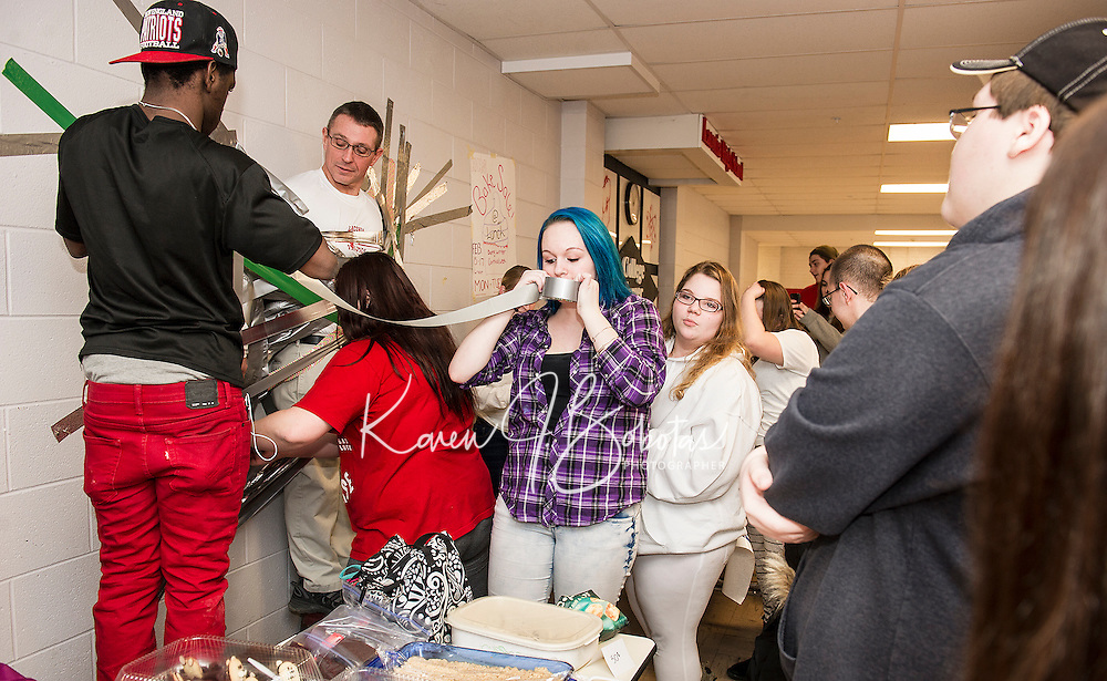 Justice Glover, Lucy Tully, Britney Waycott and Mariah DeRoche duct taping Craig Kozens Athletic Director/Dean of Students to the wall as Jag students raise money for the Make-A-Wish Foundation on Wednesday afternoon at Laconia High School.  (Karen Bobotas/for the Laconia Daily Sun)