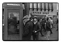 Men waiting outside a telephone box, White Hart Lane, London, 1982. South-East London, 1982