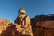 Two people exit Surb Astvatsatsin (Holy Mother of God) Church in Noravank, Armenia. In addition to its overall design, the church, completed in 1339, is famous for the narrow steps leading up to the entrance.