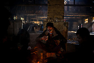 A migrant drinking some tea inside the wearehouse where hundreds live. Air inside the wearhouse is saturated with smoke from the bone fires. March 17th, 2017, Belgrade, Serbia. Federico Scoppa