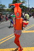 A woman in a bright orange shrimp costume, carying a large goblet of shrimp cocktail.