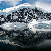 The icy and rocky scenic landscape mountains covered in ice and snow at  Neko Harbour on the Antarctic Peninsula is reflected on glassy mirror-like calm waters.