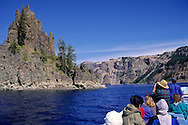 Tourists taking photos of the Phantom Ship from boat tour, Crater Lake, Crater Lake National Park, Oregon