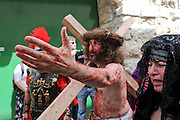 Israel, Jerusalem The Via Dolorosa Procession, Good Friday, Easter 2010 Pilgrims Re enacting Jesus covered in blood, bearing the Cross on his way to crucifixion. April 02 2010