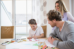 Boy drawing a picture with parents at table