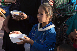 Licensed to London News Pictures. 22/10/2016. A young Iraqi girl, one of hundreds of newly arrived refugees coming from areas where the Mosul Offensive is taking place, waits to be given food by an aid worker in a school at the Dibaga refugee camp near Makhmur, Iraq. Upon arriving at the camp women and children stay in the school for around 10 - 15 days whilst completing the registration process.<br />