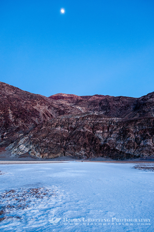 United States, California, Death Valley. Badwater is a salt flat 86 meters (282 ft) below sea level. Just after sunset with the moon hanging over the mountains.