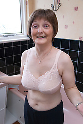 Woman who has had a mastectomy; the removal of a breast in response to breast cancer; wearing a postmastectomy; or prosthesis; bra in her bathroom,
