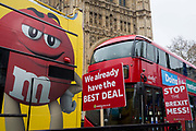 On the day that Theresa May meets with her cabinet to prepare for a No Deal Brexit, pro-EU placards and a tour bus plus a commuter bus opposite parliament in Westminster, on 2nd march 2019, in London, England. From left to right: Nigel Farage, Jacob Rees-Mogg, Chris Grayling, Jeremy Corbyn, Prime Minister Theresa May and Boris Johnson.