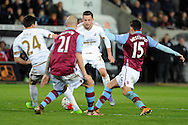 Swansea's Gylfi Sigurdsson (c) is challenged for the ball. Barclays Premier league match, Swansea city v Aston Villa at the Liberty Stadium in Swansea, South Wales on Saturday 19th March 2016.<br /> pic by  Carl Robertson, Andrew Orchard sports photography.