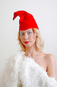 young model with red cap and white fur coat on white background