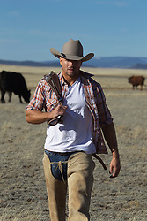 good looking cowboy walking on a cattle ranch in New Mexico