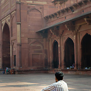 Indian man sitting in courtyard at mosque