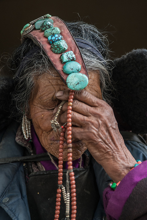 """An elderly Ladakhi woman wearing a """"perak,"""" a headdress adorned with turquoise stones, and holding Buddhist prayer beads to her forehead."""