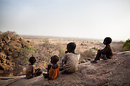 Children set outside the cave they've been forced to move to outside the town of Tess after it was razed by SAF forces.