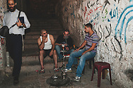 Jerusalem - October 19, 2010: Shortly before ten o'clock at night, three Palestinian men smoke shisha in an alley in the Muslim Quarter of Jerusalem's Old City. A Jewish man walks past them carrying a book of Rabbi Abraham Isaac Kook's notes. Kook, a father of religious Zionism who died in 1935, was the first Ashkenazi Chief Rabbi of British Mandatory Palestine.