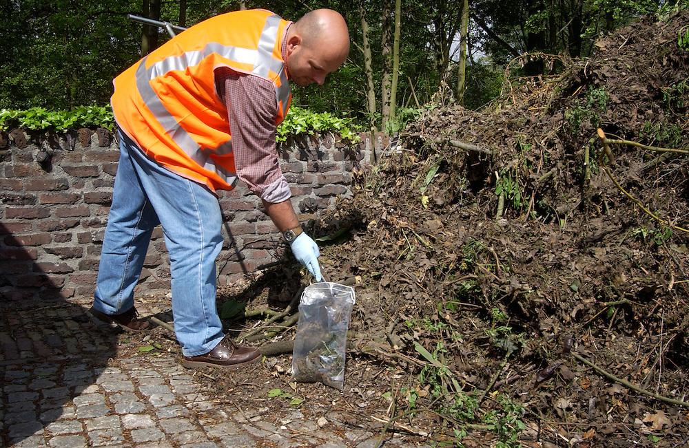 Utrecht, 12 mei 2004.Medewerker van milieudienst bemonstert en hoop illegaal gestort (tuin) afval om te kijken of er ook nog gevaarlijke stoffen in zitten..handhaving milieu..Foto (c) Michiel Wijnbergh, Driebergen