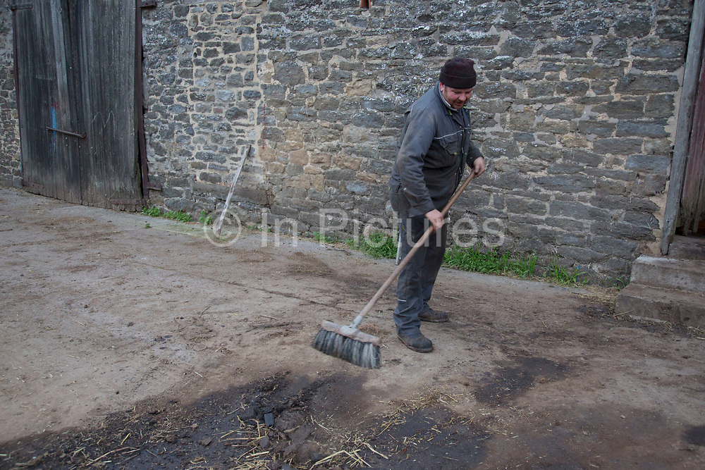 Farmer Roger Banks sweeping up outside the workshop.  Wildon Grange Dairy Farm, Coxwold, North Yorkshire, UK. Owned and run by the Banks family, dairy farming here is a scientific business, where nothing is left to chance. From the breeding, nutrition and health of their closed stock of Holstein Friesian cows, through to the end product, the team here work tirelessly, around to clock to ensure content and healthy animals, and excellent quality milk.