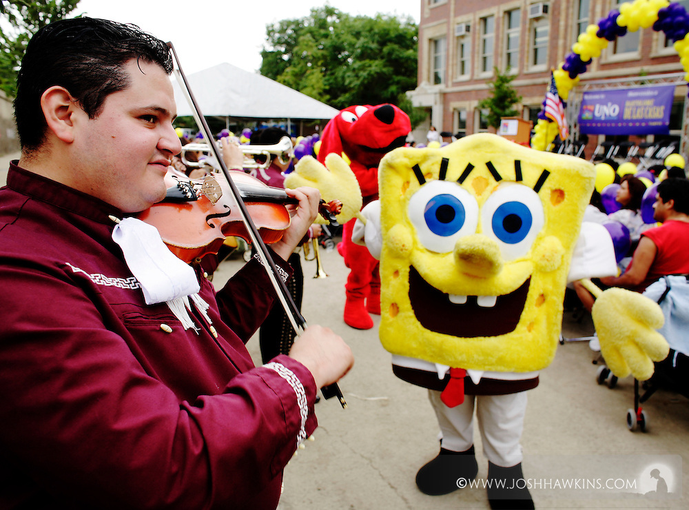 Ricardo Martinez plays violin with a mariachi band for the crowd, and Sponge Bob Square Pants runs around in the background during an opening ceremony for Bartolome de las Casas, a charter school in the Pilsen neighborhood of Chicago,  IL.  .