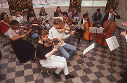 Members of secondary school orchestra practising in classroom,