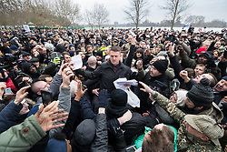 """© Licensed to London News Pictures . 18/03/2018 . London , UK . TOMMY ROBINSON (centre) hands out copies of the speech to the crowd . 1000s including supports of alt-right groups such as Generation Identity and the Football Lads Alliance , at Speakers' Corner in Hyde Park where Tommy Robinson reads a speech by Generation Identity campaigner Martin Sellner . Along with Brittany Pettibone , Sellner was due to deliver the speech last week but the pair were arrested and detained by police when they arrived in the UK , forcing them to cancel an appearance at a UKIP """" Young Independence """" youth event , which in turn was reportedly cancelled amid security concerns . Photo credit: Joel Goodman/LNP"""