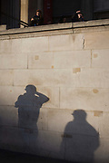 Young people whose shadows are on the wall of the National Portrait Gallery in Trafalgar Sq, London. Passers-by walk past and squint into a low sun on this winter's day as tourists above take pictures on the cityscape below them, a famous landmark in the UK's capital. The wall belongs to the southern frontage of the National Portrait Gallery in Westminster.