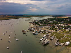 The sun attempts to break through the clouds as it sets at at West Mersea, Mersea Island, near Colchester in Essex. West Mersea, Essex, July 11 2019.