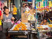 23 AUGUST 2014 - BANGKOK, THAILAND:          A woman walks past a vendor selling fruit on the sidewalk along Chareon Krung Road in Bangkok. The Thai military junta, formally called the National Council for Peace and Order (NCPO), has ordered street vendors off of the sidewalks in an effort to bring order to Bangkok's chaotic sidewalks. Vendors have complained that the new regulations are hurting them economically but largely complied with the military orders.   PHOTO BY JACK KURTZ