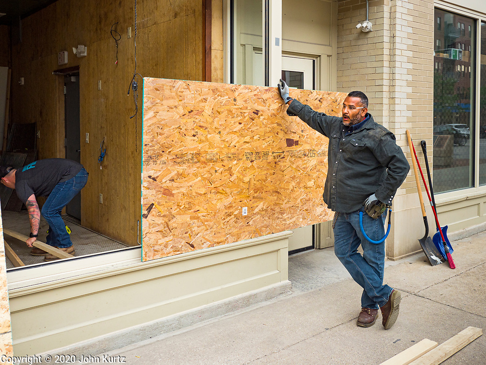 31 MAY 2020 - DES MOINES, IOWA: A worker holds a sheet of plywood over the shattered window of a pizza restaurant and bar in downtown Des Moines. A group of rioters, protesting the death of George Floyd in police custody in Minneapolis, smashed windows in businesses and restaurants around the Polk County Courthouse in Des Moines. Des Moines police said they made 25 arrests Saturday night and very early Sunday morning. No one was hurt in the disturbances.      PHOTO BY JACK KURTZ