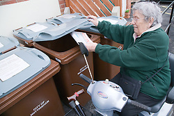 Older woman recycling newspapers,