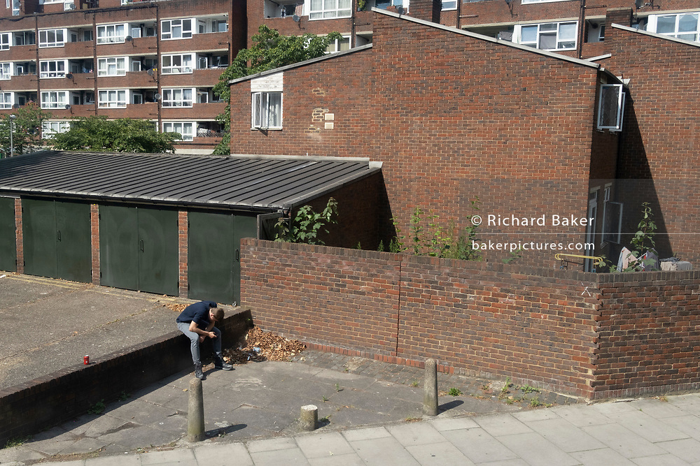 A solitary man is slumped to read his phone during the summer heatwave, next to estate homes in Southwark on Covid 'Freedom Day'. This date is what Prime Minister Boris Johnson's UK government has set as the end of strict Covid pandemic social distancing conditions with the end of mandatory face coverings in shops and public transport, on 19th July 2021, in London, England.