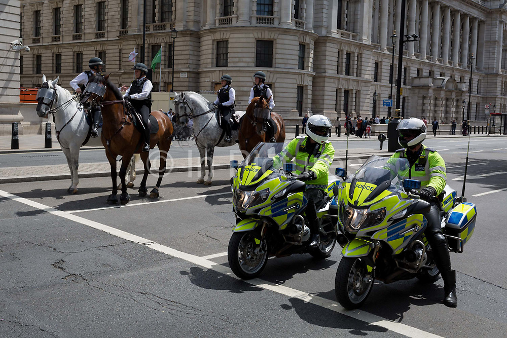 On US President Donald Trumps first day of a controversial three-day state visit to the UK by the 45th American President, mounted British Met Police officers on horseback and motorbikes secure Whitehall, on 3rd June 2019, in London England.