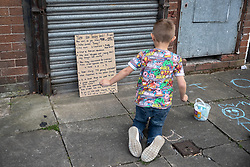 © Licensed to London News Pictures . 22/05/2019. Salford, UK. A child uses chalk to draw on the pavement beside a placard criticising Yaxley-Lennon , at the rally . Former EDL leader Stephen Yaxley-Lennon (aka Tommy Robinson ) holds a campaign rally at the derelict Mocha Parade shopping precinct in Salford , opposed by anti-fascists . Yaxley-Lennon is running for a seat in the European Parliament representing the North West of England . Photo credit: Joel Goodman/LNP