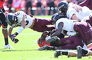 Southern Illinois Salukis safety Boo Rodgers (29) leaps over a pile of teammates as they bring down the ball carrier in first quarter action. The Southern Illinois University - Carbondale (SIUC) Salukis defeated the host Southeast Missouri State University (SEMO) Redhawks 36-19 in an NCAA football game at Busch Stadium on Saturday September 21, 2013.