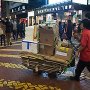 A woman pushes a trolley loaded with cardboard through Times Square, busy with Christmas shoppers. 7 million people live on 1,104km square, making it Hong Kong the most vertical city in the world.
