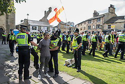 © Licensed to London News Pictures . 02/09/2017 . Keighley , UK . Police detain and handcuff an EDL protester and take his dog from him at the demonstration . Far-right street protest movement , the English Defence League ( EDL ) , hold a demonstration in the West Yorkshire town of Keighley , opposed by anti-fascists , including Unite Against Fascism ( UAF ) . The EDL say they are demonstrating against the sexual grooming and abuse of English girls by Muslim men and against terrorism across the UK . Photo credit : Joel Goodman/LNP