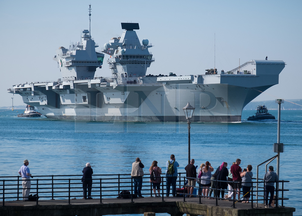 © Licensed to London News Pictures. 23/06/2018. Portsmouth, UK.  People watching as the Royal Navy's flagship, HMS Queen Elizabeth, sails into Her Majesty's Naval Base (HMNB) Portsmouth this morning, 23rd June 2018.  The aircraft carrier has been performing trials in the Northern Atlantic, including her first replenishment at sea. She is expected to remain in Portsmouth ahead of aircraft trials off the coast of the United States later this summer.Photo credit: Rob Arnold/LNP