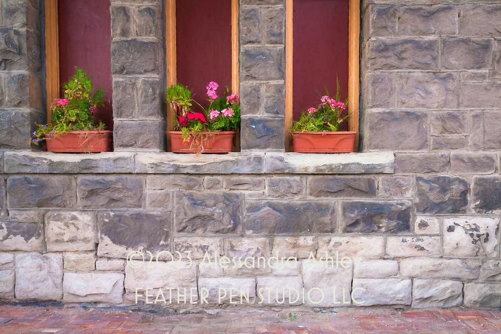 Flower boxes on stone ledge outside church building, Butte, MT.