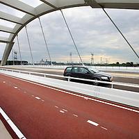 Nederland, Amsterdam , 25 juli 2014.<br /> Verbindingsweg tussen stadsdeel IJburg en snelwegen A1 en A9 is vannacht opgersteld.<br /> IJburg krijgt over een jaar een nieuwe ontsluiting aan de oostkant van het eiland. De laatste werkzaamheden voor de Oostelijke Ontsluiting IJburg (OOIJ) zijn medio november van start gegaan. De OOIJ verbindt de stadswijk rechtstreeks met de snelwegen A1 en A9. De vierbaansweg krijgt een gedeeltelijk vrijliggende busbaan. Naast het autoverkeer zullen ook fietsers en het hoogwaardig openbaar vervoersnetwerk, waaronder de Zuidtangent Oost, gebruik maken van de verbinding. Na de zomer van 2014 wordt deze nieuwe toegangspoort tot Amsterdam opengesteld.<br /> Foto:Jean-Pierre Jans