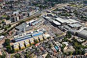 Nederland, Overijssel, Hengelo, 30-06-2011; Hart van Zuid met station en Lansinkveld. De fabriekshal van voormalige gieterij van Stork, nu ROC Twente (met gele zonweringen). Het voormalig Hijsch-complex, waarvan de spanten nog staan, is parkeerterrein. Rechts hiervan het kerngebied met fabrieken  en kantoren van Stork en Siemens. Het gebouw met de toren is de Brandweerkazerne. .railway station and Lansinkveld, part of the 'Heart of South' development scheme. The former foundry of Stork is now ROC Twente (technical and vocational training). The former Hijsch complex, its rafter still standing, is used for parking. The building with the tower is the new fire station..luchtfoto (toeslag), aerial photo (additional fee required).copyright foto/photo Siebe Swart