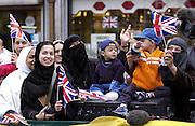 Muslim women and children in East End of London wave British Union Jack flags to demonstrate patriotic support for England, UK
