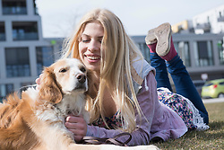 Teenage girl lying in park with her dog, Munich, Bavaria, Germany