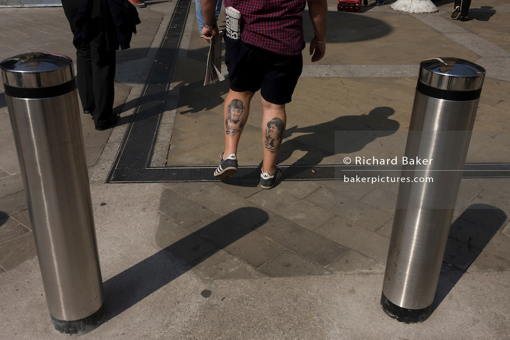 A man with Laurel and Hardy tattooes passes between two polished bollards at Liverpool Street station.